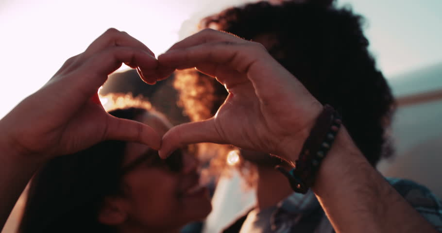 Happy young hipster couple making heart shape with hands close to a vintage van during a summertime road trip | Shutterstock HD Video #15255004