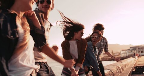 Group of multi-ethnic friends partying and dancing outside on the pier at sunset on summertime
