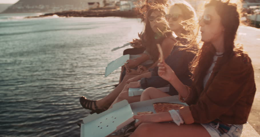 Group of hipster friends eating pizza sitting on the dock at the harbor during a summertime road trip | Shutterstock HD Video #15255091