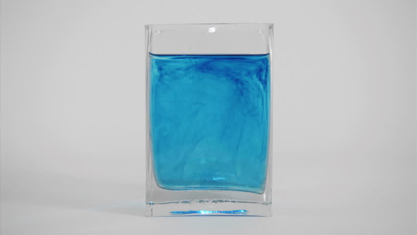 Blue dye diffuses through a glass of water.