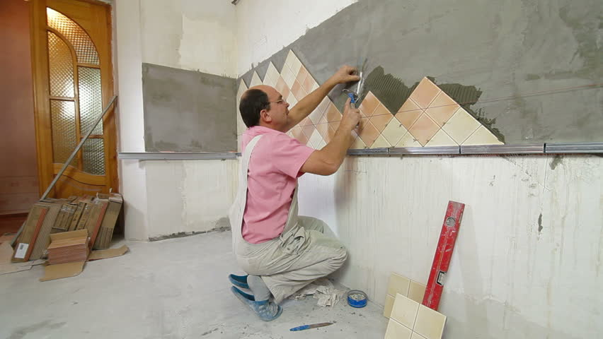 Mans Hands Installing Ceramic Tile To A Kitchen Wall Close up