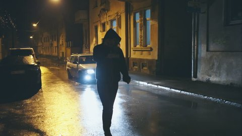 Woman with a hood, is a night city street after rain
