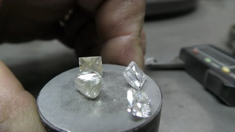 RAMAT GAN, ISRAEL - FEBRUARY 16, 2016: A polisher displays four different phases of diamond polishing, from rough to finished,  during International Diamond Week