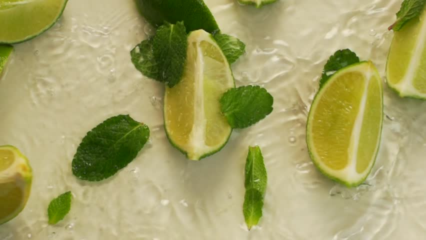 Lime and mint leaves fall into the water.