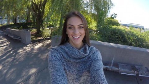 POV 4K GoPro Young happy satisfied millennial couple beautiful woman outdoors takes boyfriend husbands hand and spins around. Woman could be taking selfie spinning around to show friends social media.
