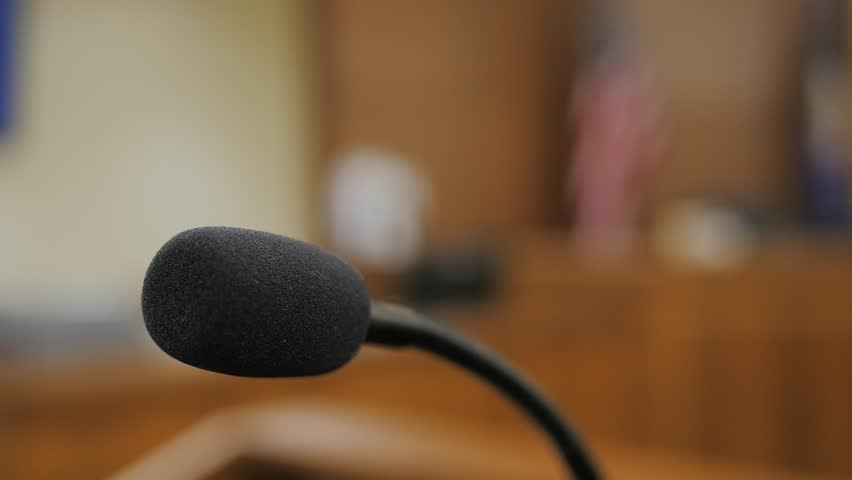 From the podium looking at the judges seat and flags in the background this close up of a microphone offers a great shot regarding sworn testimony before the court.