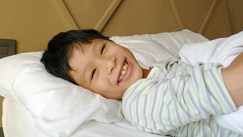 Young Asian Boy Sleeping On Bed And Smiles After Wake Up -5440