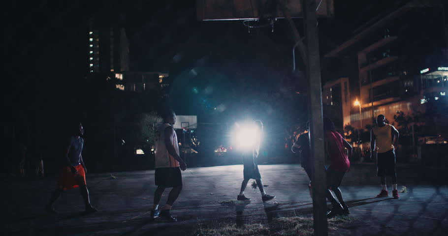 African American basketball players playing in inner-city court during nighttime with single light in background