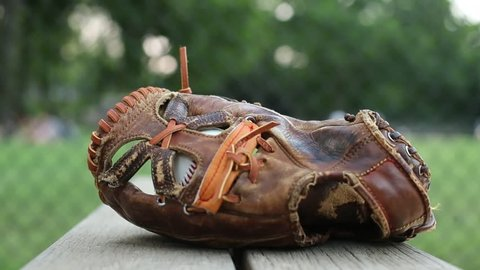 A basesball glove is picked up off a little league bench in a park / New York, New York - USA., June, 2014