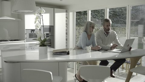 Adult male with senior female looking at personal finance in kitchen