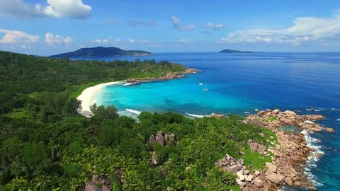 Aerial view (landscape) of tropical paradise beach (coast) with white sand and azure sea water (Indian Ocean), summer sunny day, Grand Cocos, La Digue, Seychelles islands vacation, UHD 4K