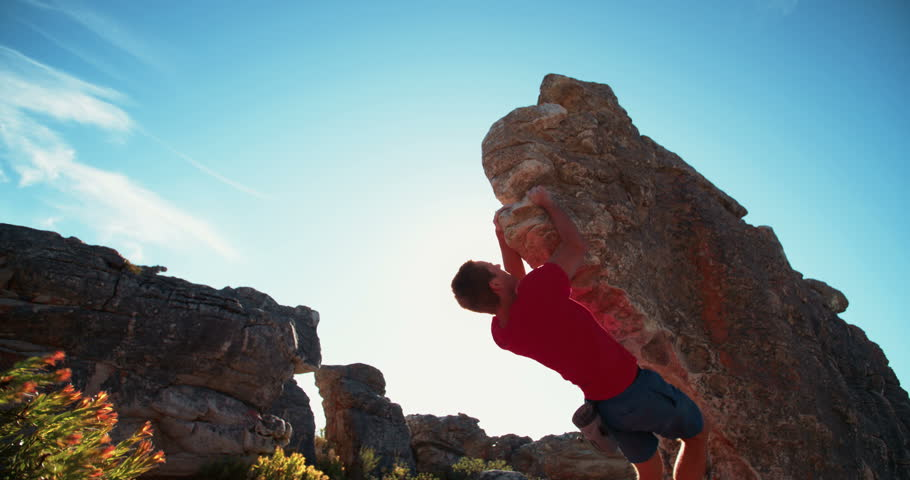 Confident rock climber conquering the challenge of bouldering on a sunny day. He is fit, strong and focussed on the ascent of the mountain.