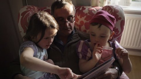 A grandfather is reading a story book to his granddaughter and grandson. The grandson is dressed up as a princess from the story in the gender blender style. Shot in a modern British house.