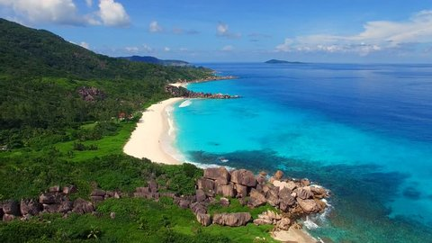 Aerial view (landscape) of tropical paradise beach (coast) with white sand and azure sea water (Indian Ocean), summer sunny day, Grand Anse, La Digue Island, Seychelles islands vacation, UHD 4K