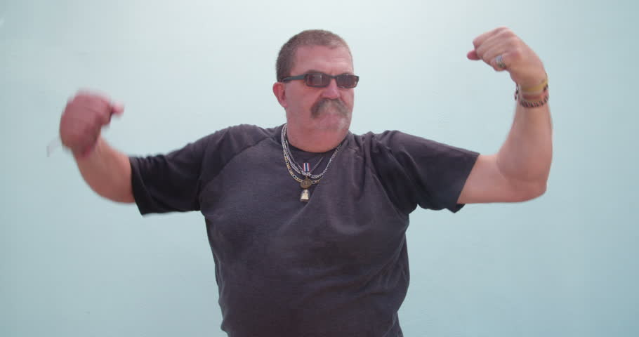 Funny senior adult man with sunglasses showing his big arms, isolated on blue wall background