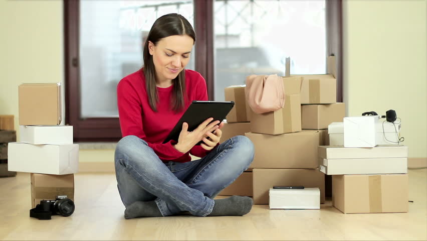 Cheerful young woman using her tablet for home shopping while sitting on the floor beside stack of boxes | Shutterstock HD Video #15413374
