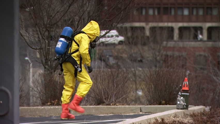 Man in hazmat suit checking testing device. HAZMAT team members wearing protective suits to protect them from hazardous materials during a nuclear or biological disaster preparedness drill.