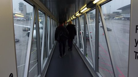 ZURICH - FEBRUARY 29, 2016: POV walk through jet bridge, boarding to airliner, look out to apron area, rainy weather outside. Unidentified passengers come ahead, Zurich Airport, morning time flight