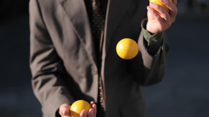 The man effortlessly juggles three balls.