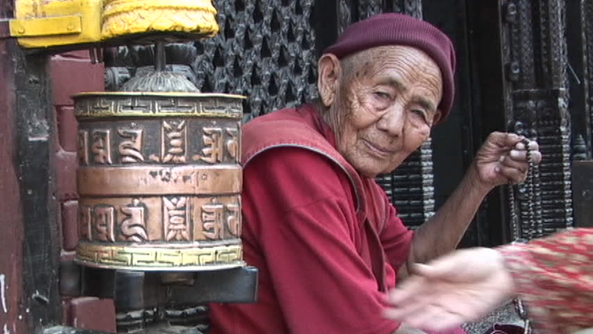 KATHMANDU, NEPAL - CIRCA 2005: Old Buddhist monk (or nun) with prayer beads next to spins prayer wheel circa 2005 in Kathmandu.
