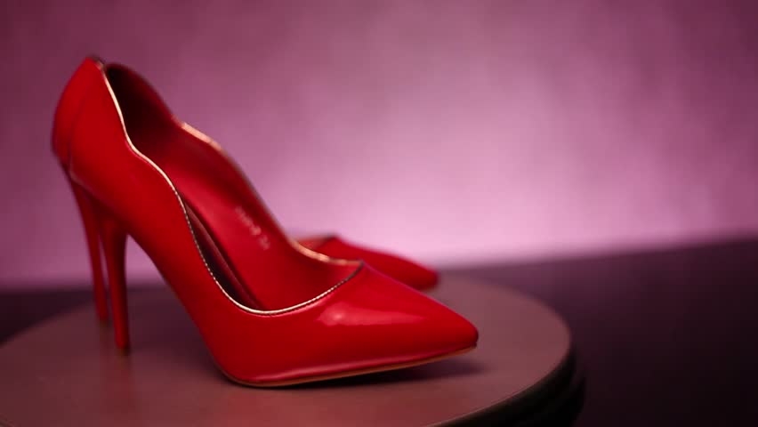 Red, glossy stiletto high heel shoes on rotating shop display with increasing light intensity