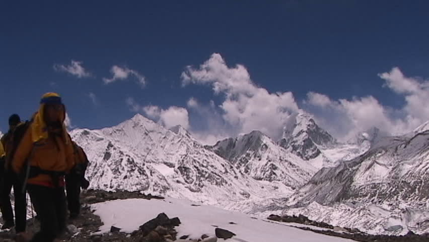 MOUNT EVEREST, TIBET - CIRCA 2005: Climbers walk towards Mt. Everest base camp with Mt. Pumori and the mountains of Nepal in the background, circa 2005 in Tibet.