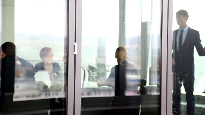 Businessman giving presentation using flipchart in conference room behind glass wall, graded