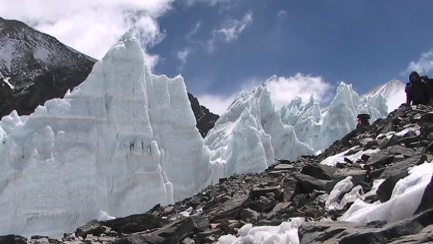 MOUNT EVEREST, TIBET - CIRCA 2005: Climbers walk in front of ice pyramids circa 2005 in Tibet.