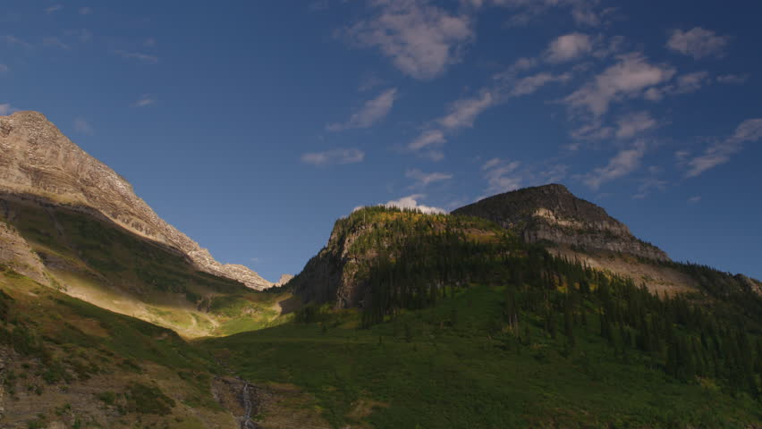 Camera pans scenic mountain peaks on Going to the Sun road in Glacier National Park.  Montana. 4K