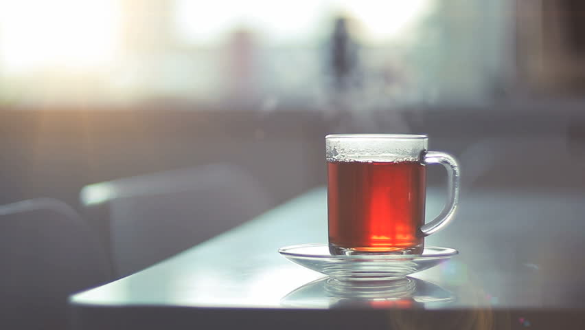 Seamless looped video with a glass of steaming hot tea on a table