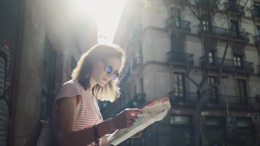 Young tourist woman exploring Barcelona map while traveling in Spain, vacation concept, flare light | Shutterstock Video #15513184