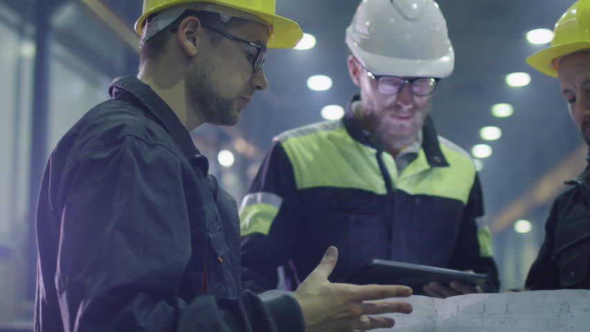Team of workers at a heavy industry factory have a conversation while looking at a blueprint. Shot on RED Cinema Camera. #15514864