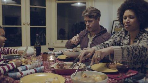 Mixed race family eating Christmas dinner