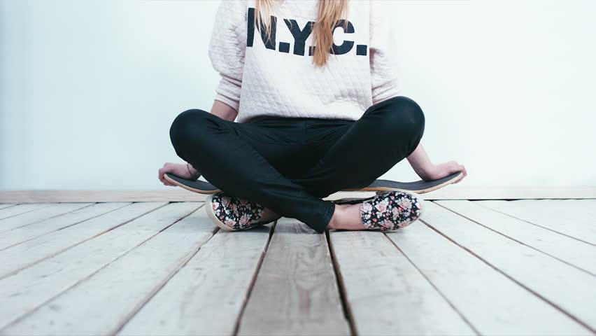 Teen girl sitting on a skateboard. 4K cinemagraph - motion photo seamless loop