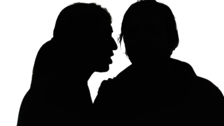 A woman whispering a secret in the ear of a man. Silhouette shot.