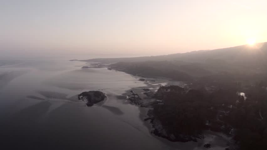 Aerial view of Scottish beach at low tide with sunset over the hills.