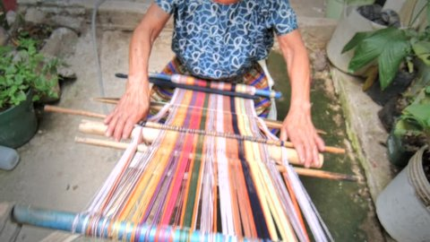Elder woman working with a waist loom to finish an handcraft to sell in the market