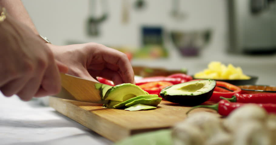 Slicing avocado in a kitchen environment. Cutting fresh vegetables on a wooden bench in a modern kitchen with shallow focus and blurred background. Strong and vivid colors.