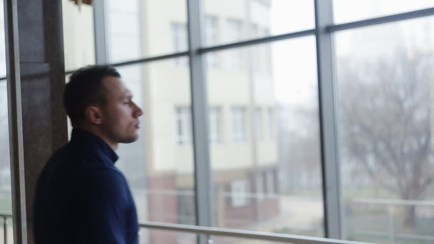 A businessman looks out the window in a contemplative way. Medium shot | Shutterstock HD Video #15551134