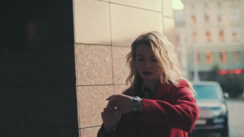 Business woman in red coat with red lips goes upstairs to business center and looks on watch,she is late for work or meeting. Steady cam shot, slow motion. | Shutterstock HD Video #15557833