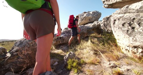Hiking man helping his girl friend climbing a rock while travelling together in sunny outdoors