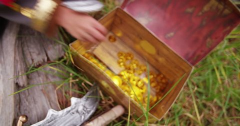 Boy dressed up as little pirate is excited to found the gold coins in treasure chest after a treasure hunt through park with his map.