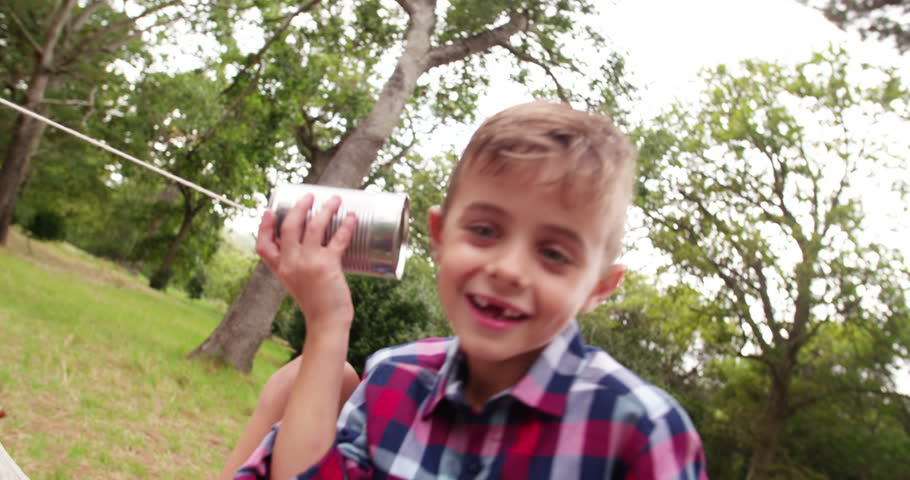 Cute little Boy curiously listening on tin can phone in park, concept for telephone or mobile communication.