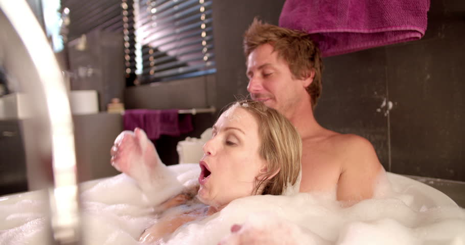 Family of dad, mom and infant daughter taking a bubble bath together with daughter