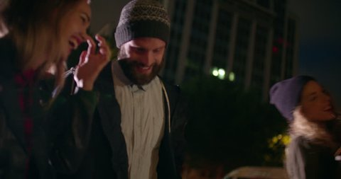 Hipster style young adult friends enjoying night city life walking and hugging together