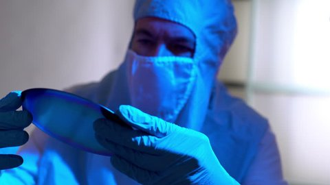 cleanroom tech checking out a silicon wafer microchip disk 4k