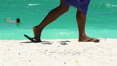 A man in flip-flops passing by on the beach. Feet close up.