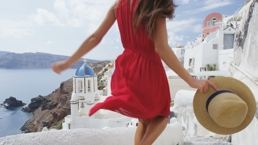 Santorini Oia Blue Dome Church. Tourist woman on travel sightseeing famous blue domed church landmark destination. Beautiful girl in red dress on visiting the Greek island. RED EPIC SLOW MOTION.