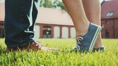 Close up of feet and legs as woman is tip toeing for a kiss. Romantic Couple kissing on a green grass lawn outdoors. Slow Motion 120 fps. Young love concept with lovers kissing. Stylish hipster shoes.