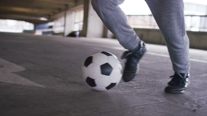 4K Feet of a skillful soccer player doing quick movements with his football